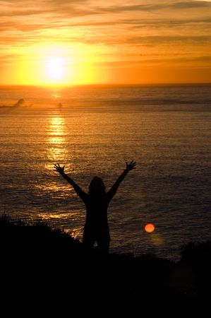 worshipping: Woman with hands upheld worshipping the sun as it sets to the west on the pacific ocean near San Francisco