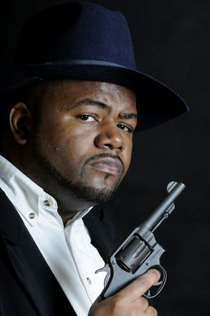 young African American man in a hat and suit and a gun photo