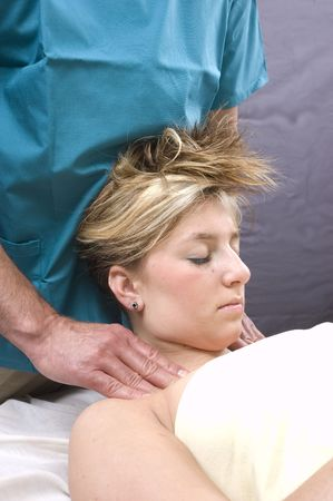 Woman getting a neck massage by a massuer photo