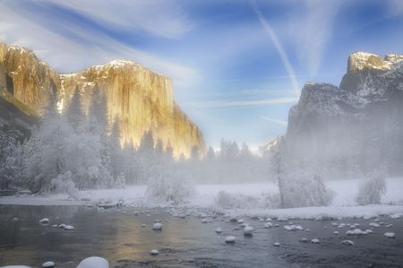 Alpenglow on the granite peaks in Yosemite valley with mist rising above the merced river photo