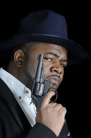 young bearded African American man with a gun isolated on a black background photo