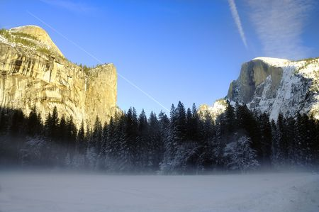 Sunset on the granite peaks in Yosemite National Park with mist rising from the snow cover floor in the valley, an airliner leaving a trail in the sky and snow on top of Half dome. photo