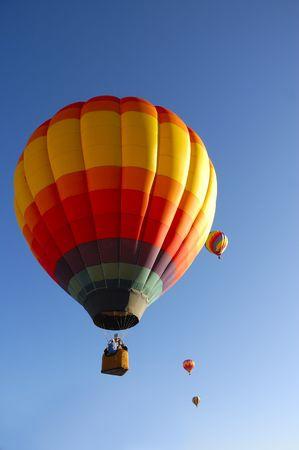 colorful balloon rising at dawn in the cold air at the Taos hot air balloon festival Фото со стока