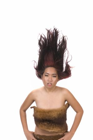 hides: Beautiful young brunette asian huntress in animal hides with hair blowing up isolated on white