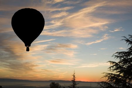 Beautiful Sunset over San Francisco Bay in California with a hot air balloons flying overhead in silhouette, with jet aircraft in the far distance photo