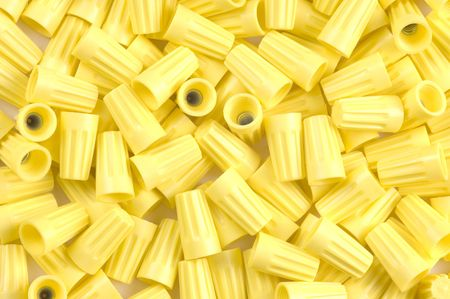 threaded: Yellow wirenuts used for connecting 12 gauge wire in household circuits as a background  Stock Photo