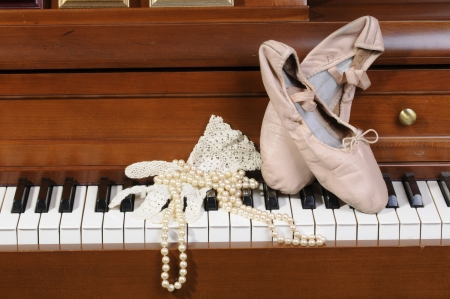 shoe strings: ballet shoes, lace glove and pearls on a piano keys