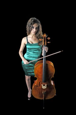 fingering: young female cellist isolated with instrument over black background