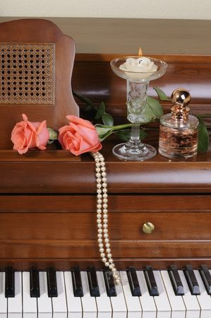 pair of peach/pink colored Roses sitting on keys of piano with candle and pearls 免版税图像