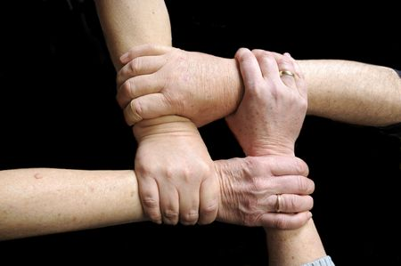 4 older freinds joining Hands in union to form a square on a black background