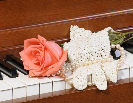 perle rose: Peach  rose de couleur rose assis sur des touches de piano avec gant de dentelle et de perles