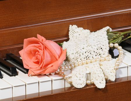 lace gloves:  peachpink colored Rose sitting on keys of piano with lace glove and pearls