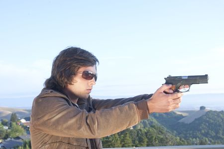 young man in leather jacket with sunglasses on and pistol pointed at target Stock Photo - 5025693