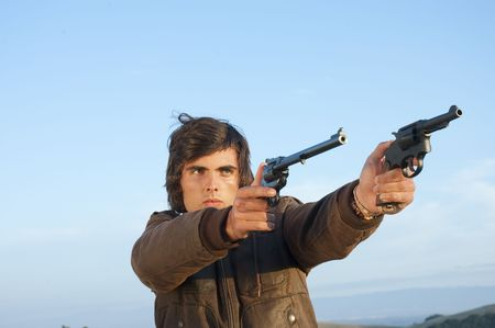 young man in leather jacket on and pistols pointed at target Stock Photo - 5025686