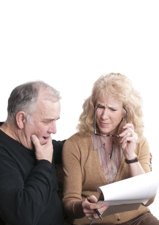 quizzical: Older couple going over accounts for retirement, isolated on white Stock Photo