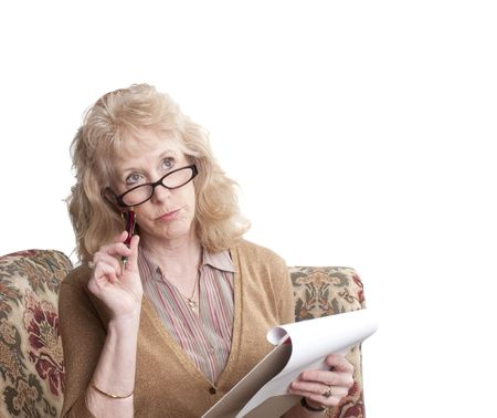 quizzical: middle-aged woman with glasses on, sitting on sofa with note pad looking perplexed,  isolated on white