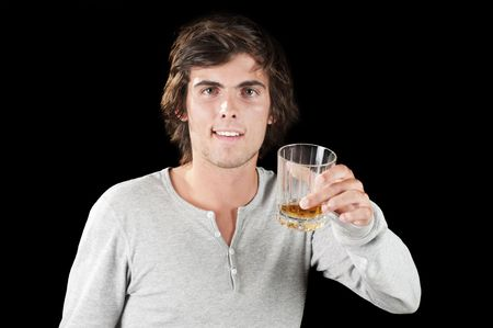 Handsome young man isolated over black with a glass of whiskey Banco de Imagens