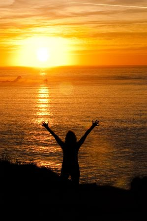 worshipping: Woamn raising hands in the air worshipping or catching the last rays of the setting sun while looking out to sea on the West coast