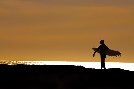 surfboard fin: surfer heading out in the setting sun for a final ride at Santa Cruz, CA