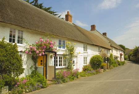 a row of picturesque thatched cottages on an English village street with flowers growing in the front Stock Photo