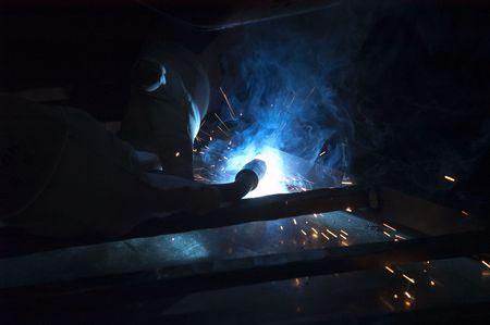 Blacksmith working on decorative handrail using a welder Imagens