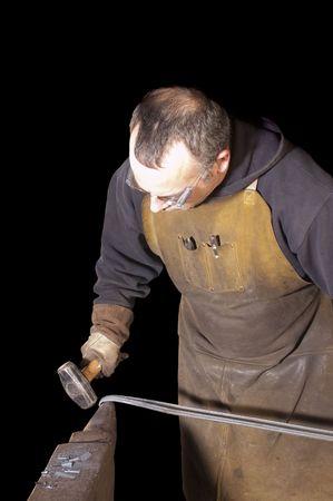 加熱鉄の poiunding によって装飾的な金属 handrai 取り組んでいる黒の上の鍛冶屋 写真素材