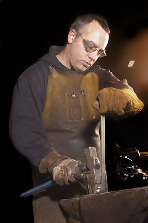 pounding: Blacksmith working on decorative handrail pounding on the heated metal