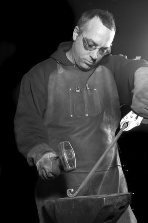 fabricating: a study of concentration, a Blacksmith working on decorative handrail beating it with a hammer into shape in black and white