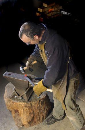 Blacksmith working on decorative handrail bending the heated metal Imagens