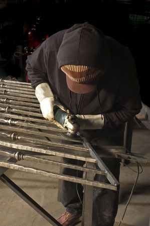 metal worker finishing welds with a grinder Imagens