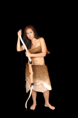 hides: Young asian woman huntress dressed in animal hides with a bow over a black background