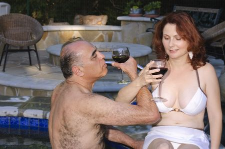 Middle-eastern Man and Hispanic woman enjoying laughter while in a hot tub photo