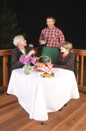 older couple in outdoor restaurant at night - waiter has served the wine to the man, to see if it is acceptable, from the look on his face it meets his requirements and is satisfactory:) photo