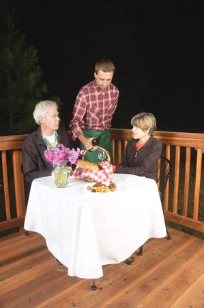 older couple in outdoor restaurant at night - waiter has served the wine to the man, to see if it is acceptable, from the look on his face it meets his requirements and is satisfactory:) Archivio Fotografico