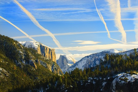 View of beautiful Yosemite valley in winter with snow covered El Capitan and Half Dome at sunset photo
