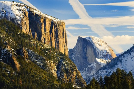 sierras: iew of beautiful Yosemite valley in winter with snow covered El Capitan and Half Dome at sunset