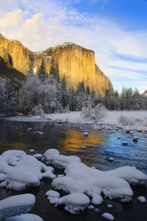 View of beautiful Yosemite valley in winter with the Merced river and snow covered El Capitan at sunset photo
