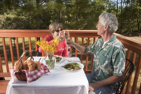 couple enjoying a dinner in an outdoor restaurant toasting each other photo