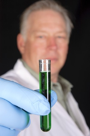chemical engineer, doctor or research scientist holding a sample of a chemical from a test tube close to  the camera to create a shallow depth of field placing the scientist out of focus behind
