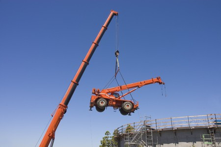 heavy equipment: Very large crane lifting small crane from inside a concrete water tank construction project Stock Photo