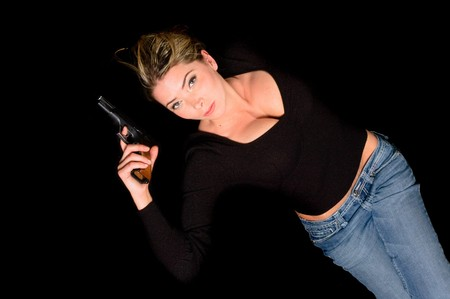 finger on trigger: buxom woman spy with handgun and finger on the trigger Stock Photo