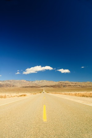 long straight road across Death Valley with a distant motor vehicvle coming towards the camera, a deep blue sky late in the afternoon, and a small puffy clouds in the sky Stock Photo - 7911535