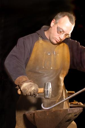 Blacksmith working on decorative handrail