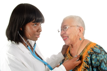 Young African American nurse or doctor checking elderly African american womans heart, isoalted on white. Reklamní fotografie