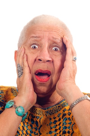 clasping: Elderly African American woman in anguish looking shocked, clasping head