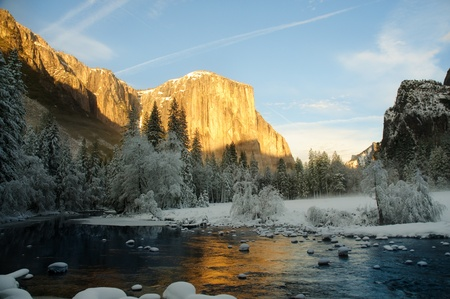 winter sunrise: Yosemite valley at sunset with golden rays of sunlight on El Capitan and beautiful reflection from the Merced river in winter Stock Photo