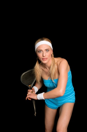 Young blond female raquetball player over a black background