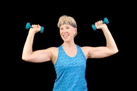 mujeres ancianas: sonriente mujer mayor ejercicio con pesas Foto de archivo