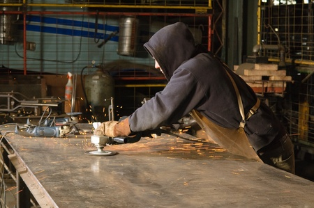 residue: Blacksmith grinding welding residue from welding table Stock Photo