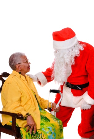 Santa talking to an African American female senior citizen isolated on a white background photo